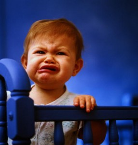 baby-standing-on-his-bed-and-crying