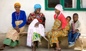 MDG : Maternal Health : group of women with babies sits outside a clinic in Rwanda